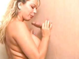 Busty Blonde Sucks A Cock Through The Gloryhole